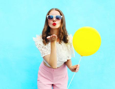 Mujer bonita en gafas de sol con el globo del aire envía un beso al aire sobre fondo azul colorido Foto de archivo