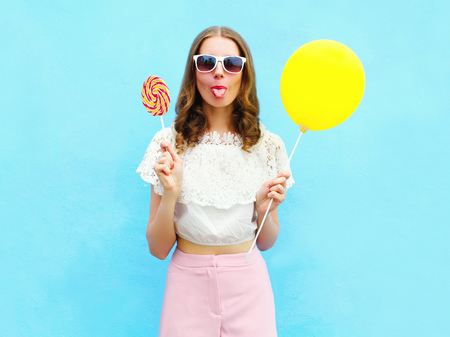 sweettooth: Fashion woman with air balloon and lollipop having fun over colorful blue background Stock Photo