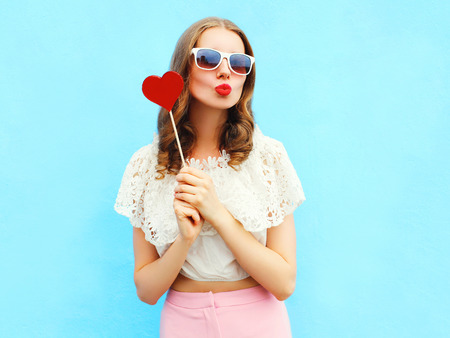 Portrait pretty woman and red lollipop over colorful blue background