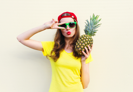 Fashion pretty cool girl model with pineapple over white background