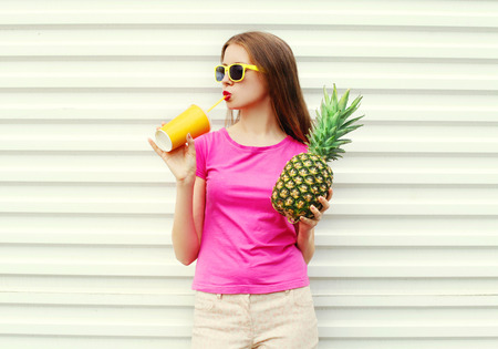 Fashion pretty cool girl with pineapple drinking from cup over white background