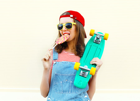 sweettooth: Fashion portrait pretty cool girl with lollipop and skateboard over white background Stock Photo