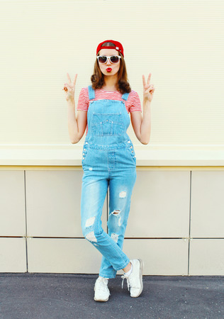 jumpsuit: Fashion pretty woman in denim jumpsuit over white background Stock Photo