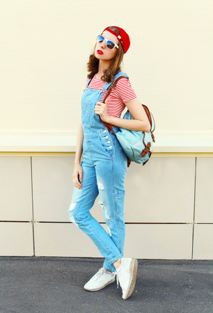 jumpsuit: Fashion pretty woman model in denim jumpsuit over white background