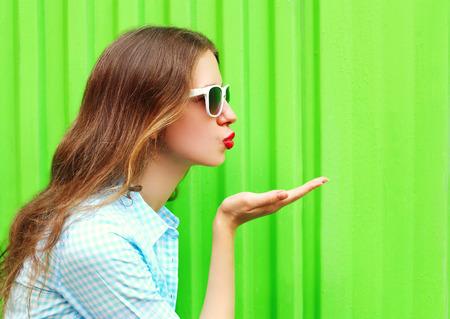 Frau in den Sonnenbrillen sendet einen Luftkuß über bunten grünen Hintergrund Standard-Bild