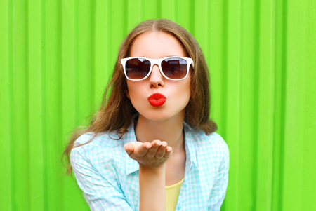 Woman in white sunglasses sends an air kiss over colorful green background Stock Photo