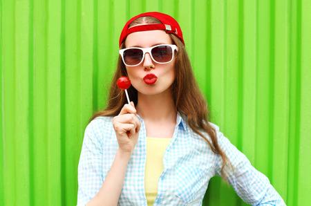 Arbeiten Sie Portrait ziemlich cool Mädchen mit Lutscher über grünem Hintergrund Standard-Bild - 59883935