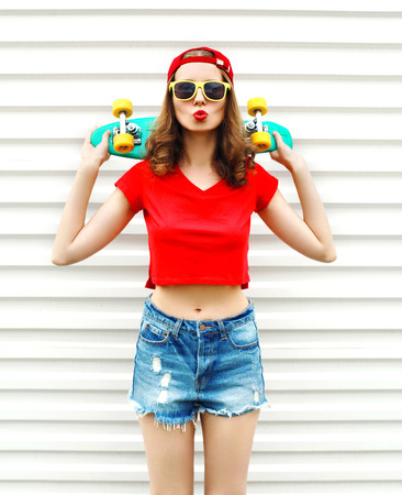 Fashion pretty cool woman in sunglasses and shorts with skateboard over white background Stok Fotoğraf