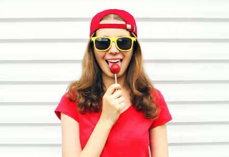 sweettooth: Fashion portrait cool girl with lollipop over white background Stock Photo