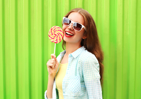 sweettooth: Portrait happy pretty smiling woman with lollipop over colorful green background