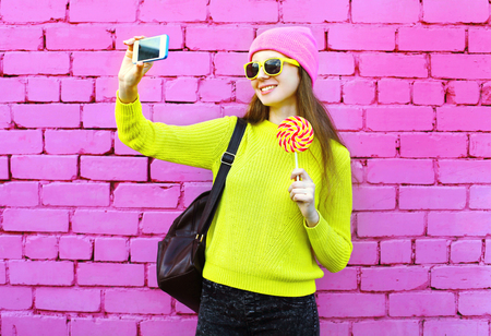 sweettooth: Fashion girl taking photo selfie portrait using smartphone over colorful pink background