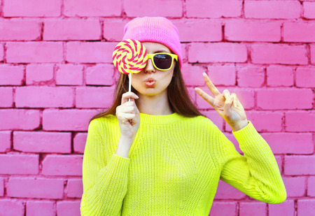 Fashion portrait pretty cool girl with lollipop having fun over colorful pink background Standard-Bild