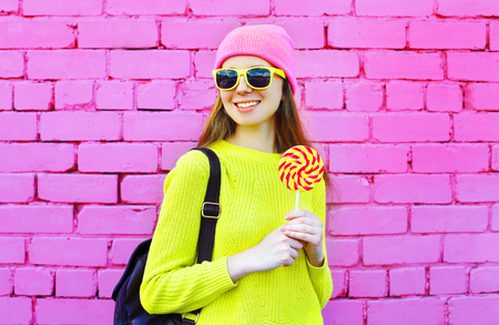 sweettooth: Fashion portrait pretty smiling girl with lollipop over colorful pink background