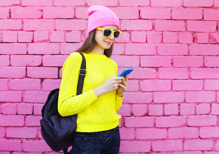 Fashion pretty cool girl using smartphone over colorful pink background