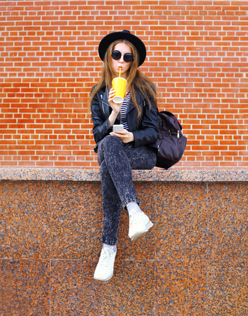Fashion pretty woman drinks juice from cup using smartphone over bricks background Banco de Imagens