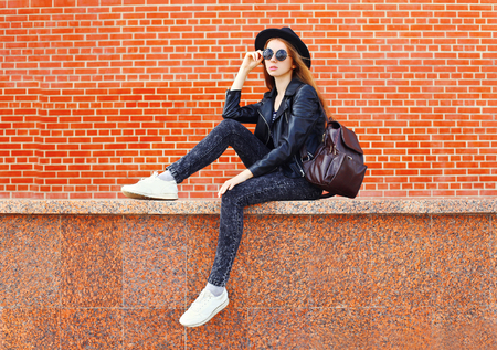Fashion pretty woman in black rock style sitting in city over bricks background Stok Fotoğraf