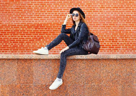 Fashion pretty woman in black rock style sitting in city over bricks background Standard-Bild