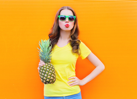 summer fruit: Fashion cool girl in a sunglasses with pineapple over colorful orange background