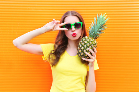 Fashion cool girl in sunglasses with pineapple over colorful orange background