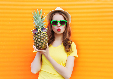 Fashion portrait cool girl in sunglasses with pineapple over colorful orange background