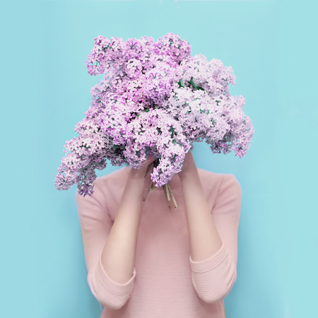 Woman hiding head in bouquet lilac flowers over colorful blue background Stok Fotoğraf - 59884052