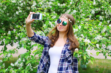 mujer hippie: Beautiful hippie woman makes self portrait on smartphone in spring flowering garden