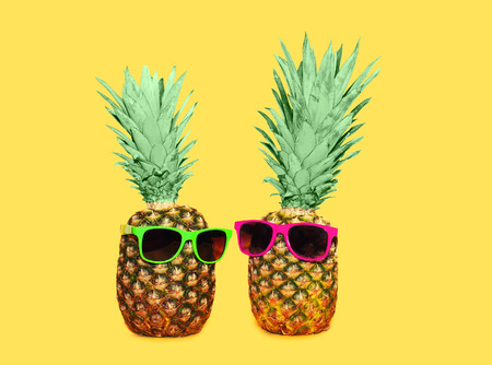 Two pineapple with sunglasses on yellow background, colorful ananas concept Stok Fotoğraf