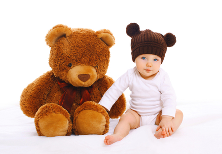 Baby with big teddy bear toy on white background