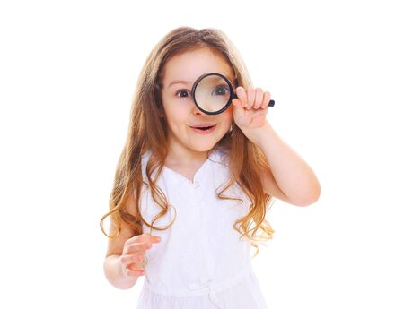 Funny little girl child looking through a magnifying glass on white background