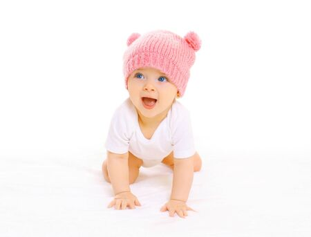 Happy cute smiling baby in knitted pink hat crawls on a white background Stok Fotoğraf