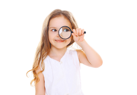 Little girl child looking through a magnifying glass on white background Standard-Bild