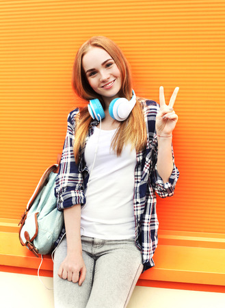 Happy pretty smiling girl with headphones listens to music having fun in city