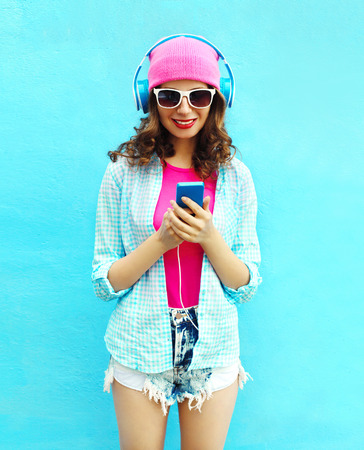 Pretty cool woman listens to music in headphones using smartphone over blue background Stok Fotoğraf