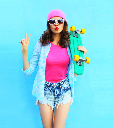 Fashion pretty cool woman in pink clothes with skateboard over colorful blue background Stok Fotoğraf