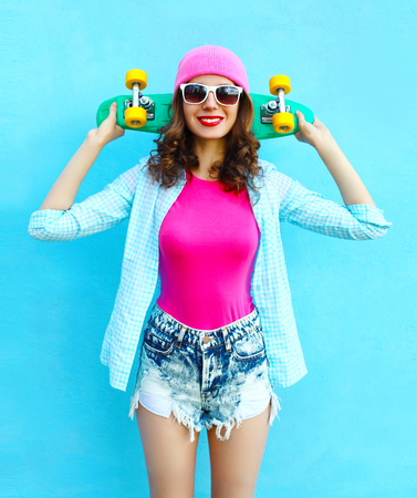 Fashion pretty cool woman in pink style with skateboard over colorful blue background