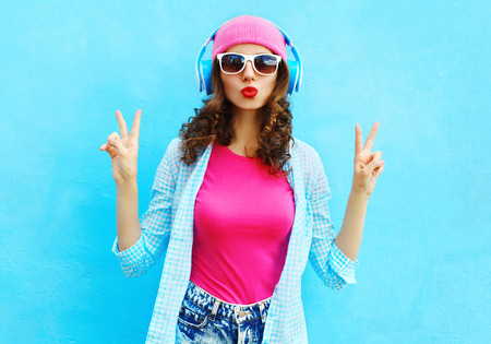 Fashion pretty cool woman listens to music in headphones over colorful blue background