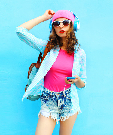 Fashion woman listens to music in headphones using smartphone over blue background
