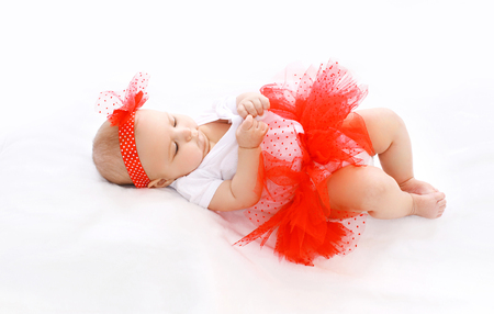bed skirt: Beautiful little girl baby in red skirt lying on bed