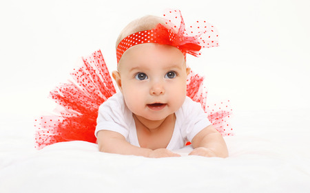 bed skirt: Portrait cute little baby girl lying in red skirt on bed Stock Photo