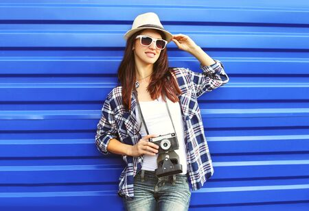 Pretty woman wearing a straw hat sunglasses checkered shirt with retro camera in city Stock Photo