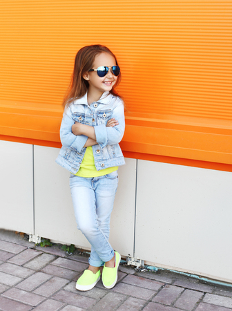 Beautiful smiling little girl wearing a sunglasses and jeans clothes in city