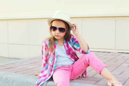 Fashion little girl model wearing a checkered pink shirt hat and sunglasses in city