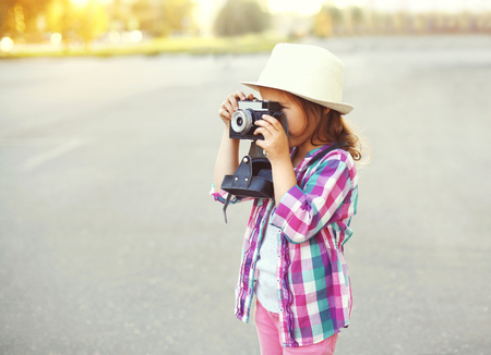 Little girl child with retro camera doing snapshot outdoors profile view