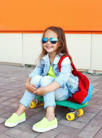 Stylish smiling little girl child with skateboard having fun in city