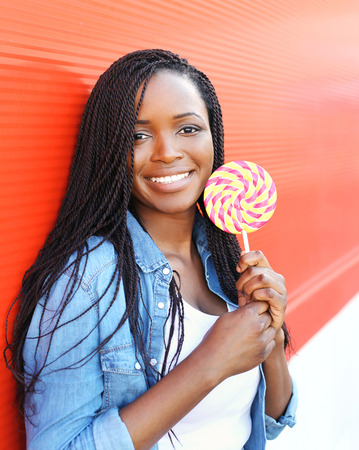 sweettooth: Happy smiling young african woman with sweet lollipop over red background