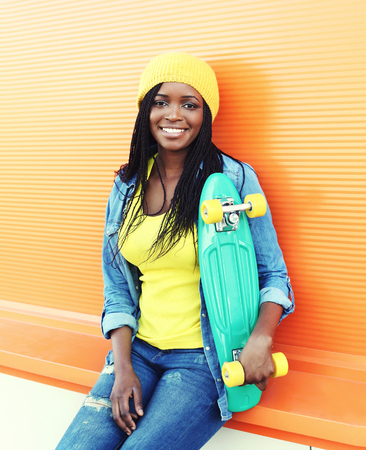 bright color: Fashion young smiling african woman with skateboard in colorful clothes over orange background