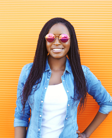 Beautiful smiling young african woman in sunglasses over orange background Stock Photo