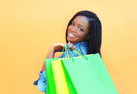 beautiful smiling african woman with shopping bags over orange background Stok Fotoğraf