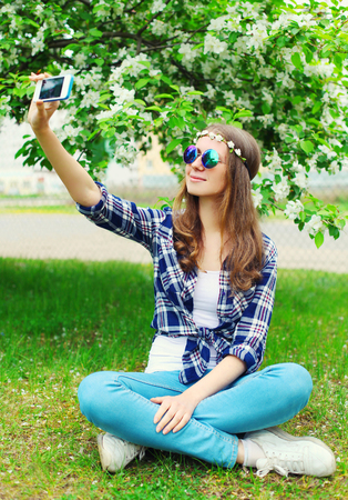 mujer hippie: Beautiful hippie woman makes self-portrait on smartphone sitting on grass in flowering garden