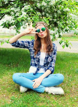 mujer hippie: Mujer de la manera fresca del hippie que se divierte en la hierba en el jardín de flores Foto de archivo